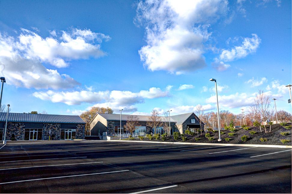 Commercial center during the day with bright blue sky and a few clouds, large empty parking lot in front