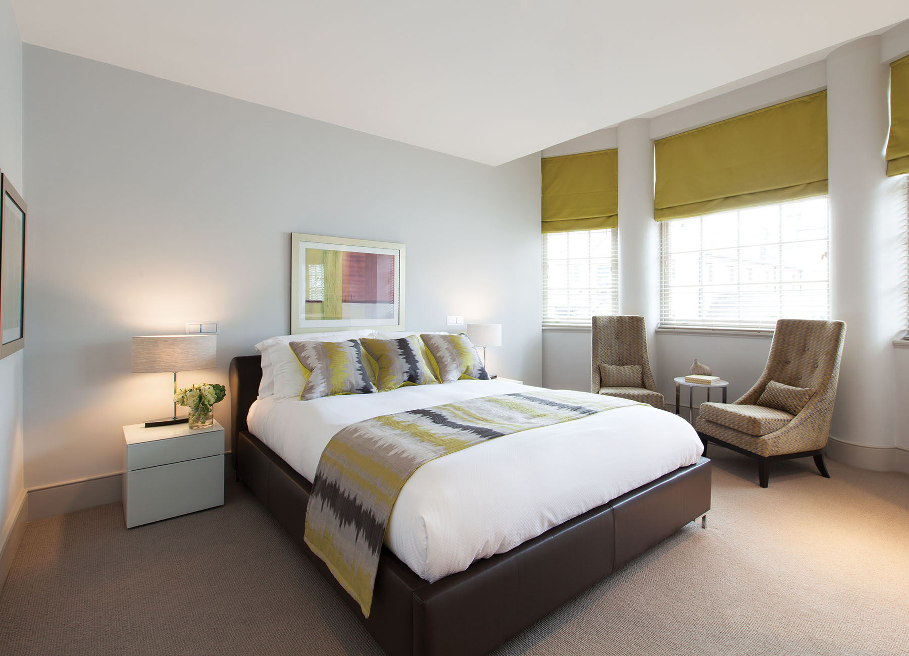 Bedroom with yellow blinds and king bed