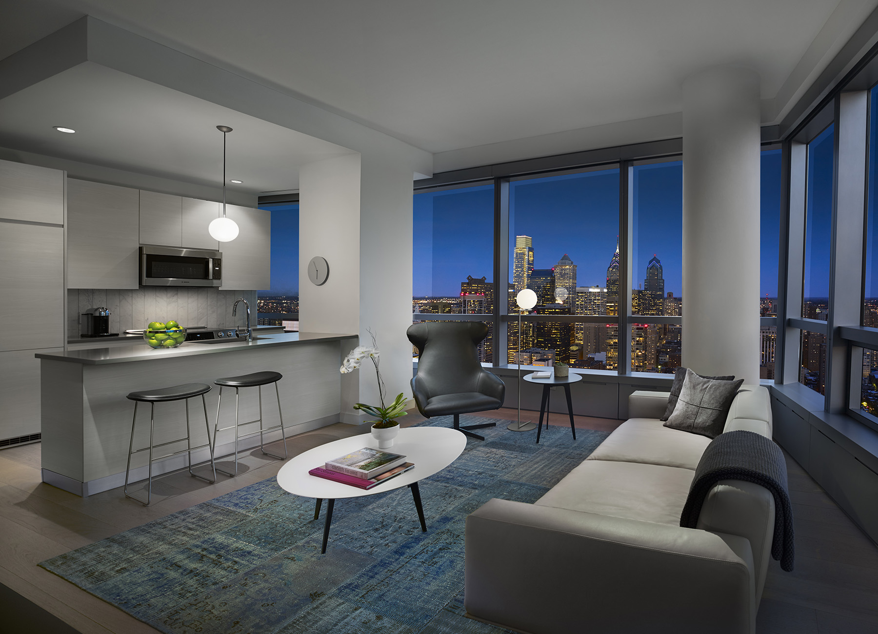 Living room with open kitchen and the Philadelphia skyline at night visible through the full length windows