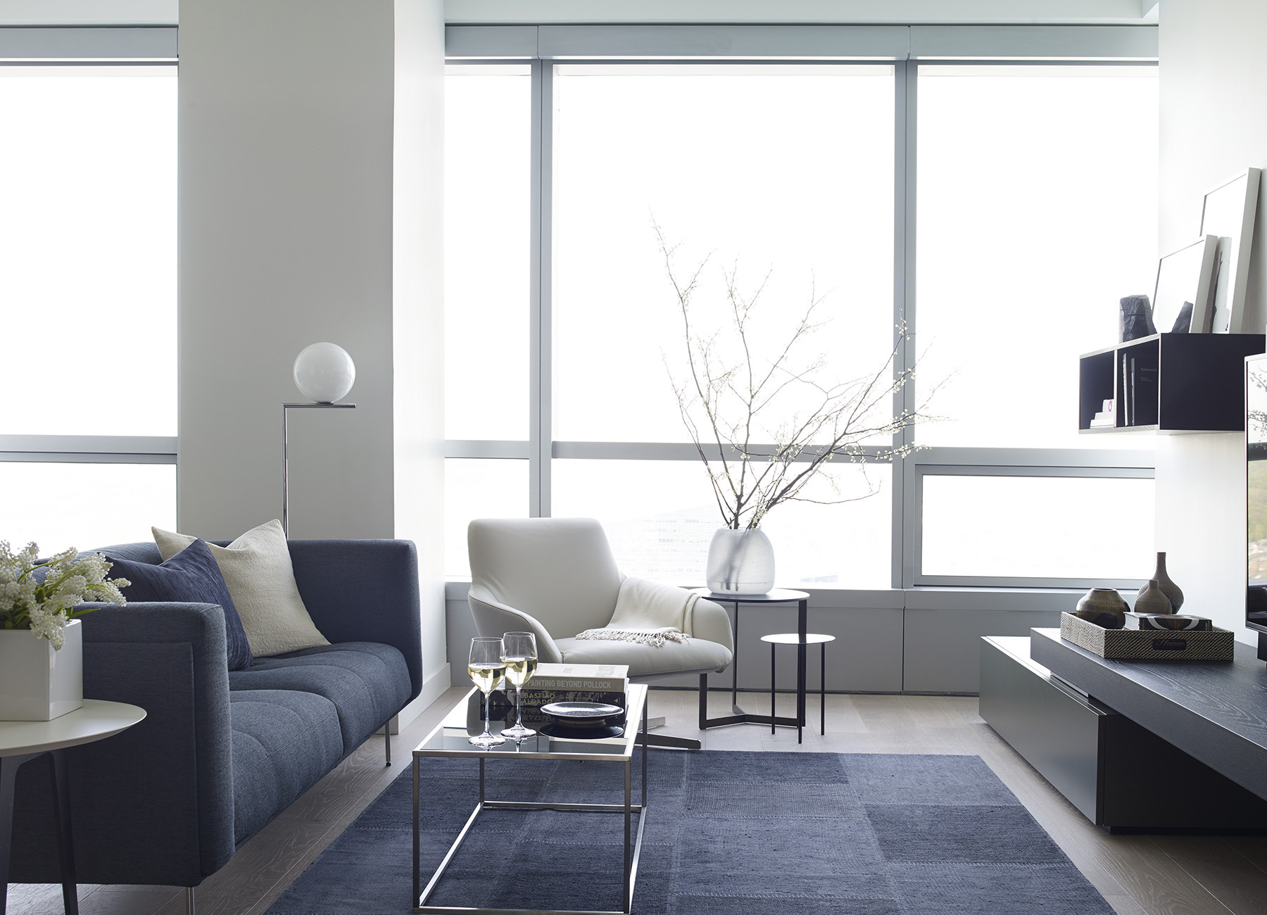 Living room with large windows and blue couch