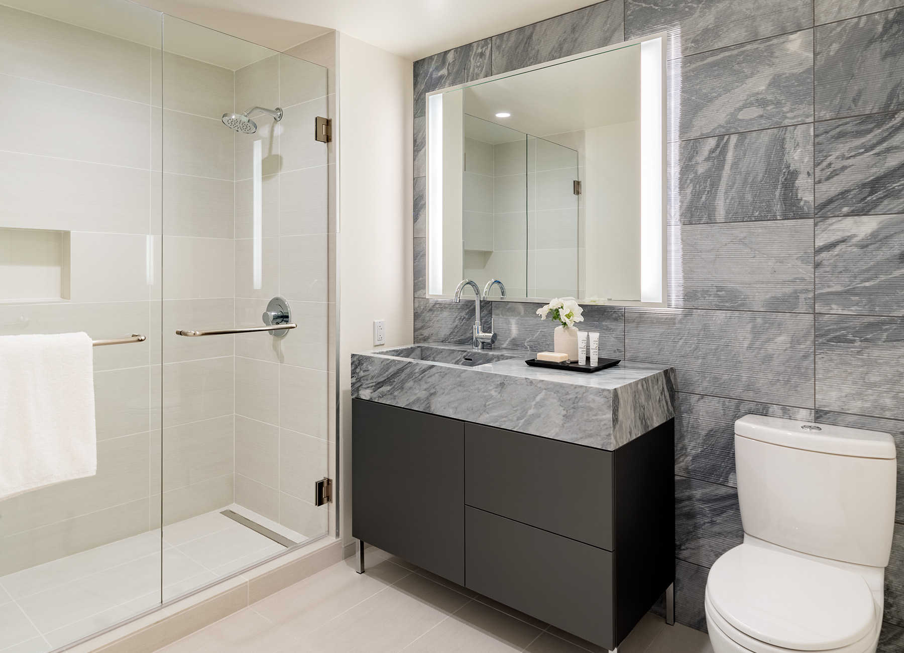 Bathroom with dark gray marble sink and white tile shower