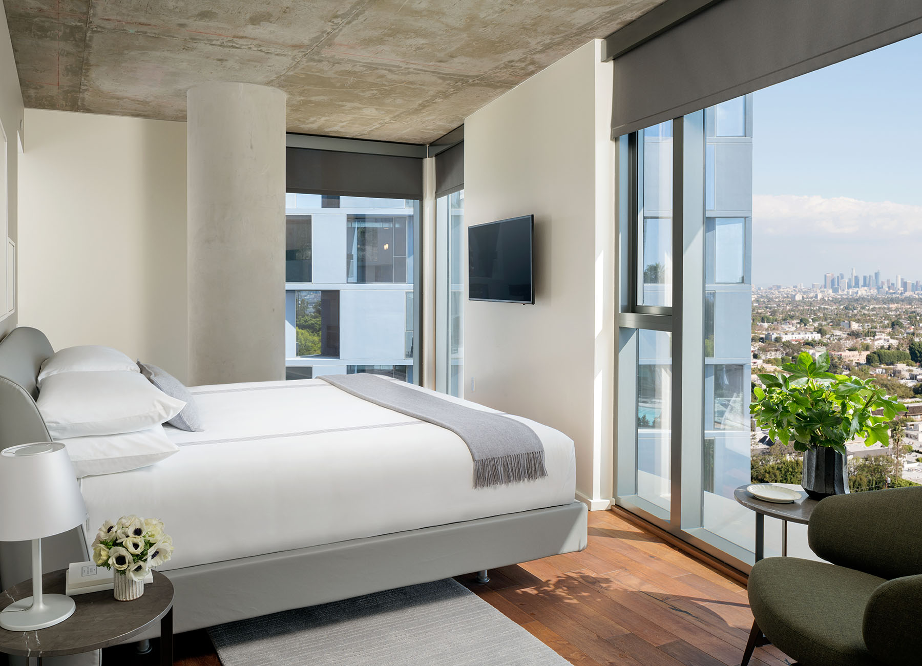 Bedroom with concrete ceiling and king bed looking over large window to West Hollywood
