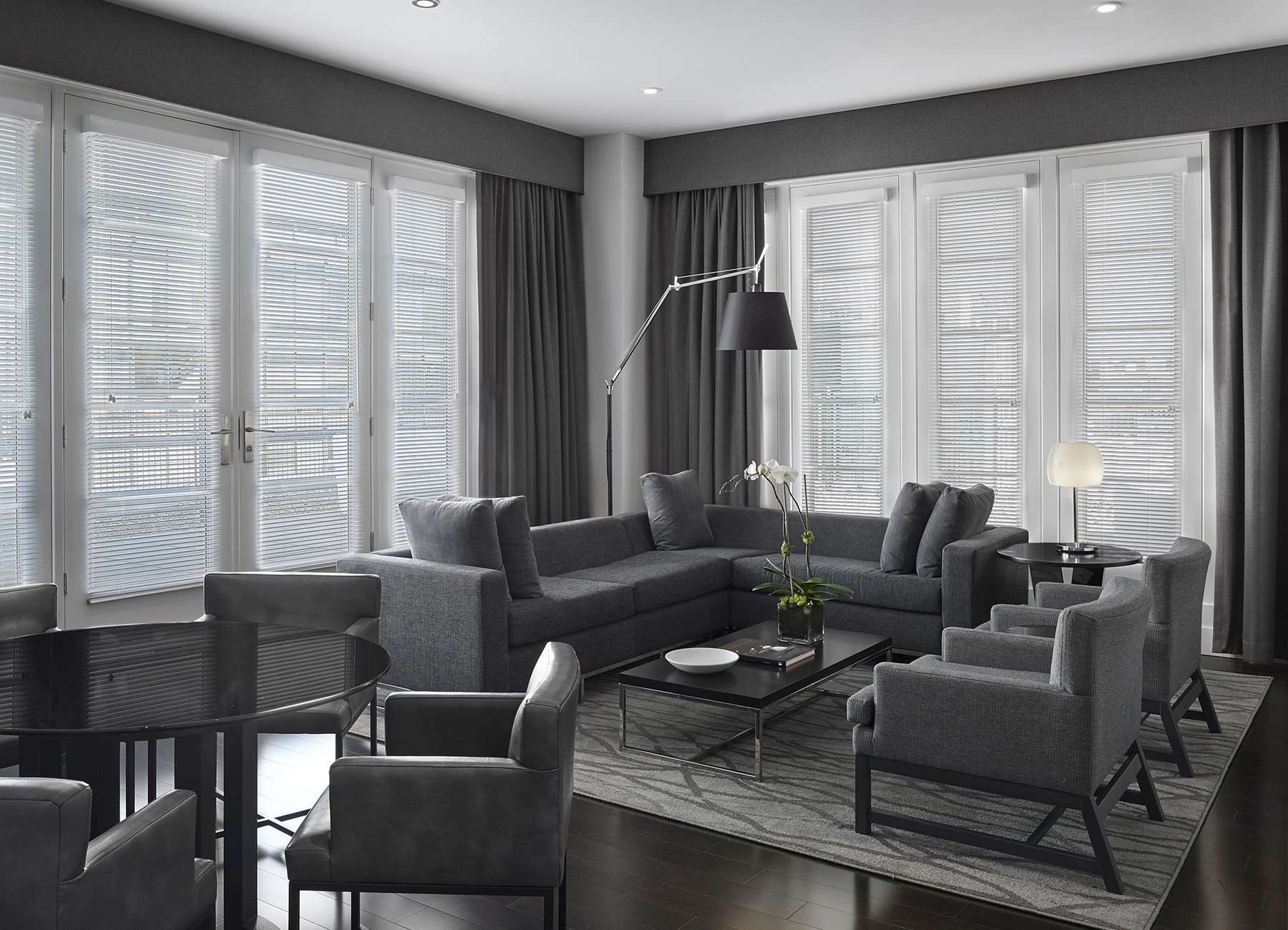 Living room with gray furniture, large windows, and gray curtains