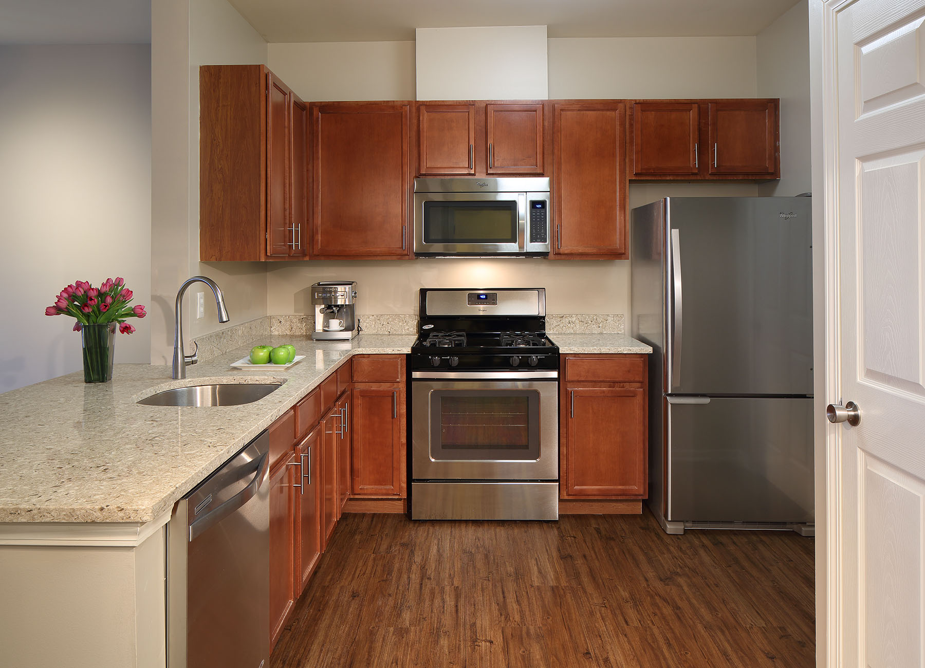 Clean kitchen with large countertops, warm wood cabinets, and stainless steel appliances