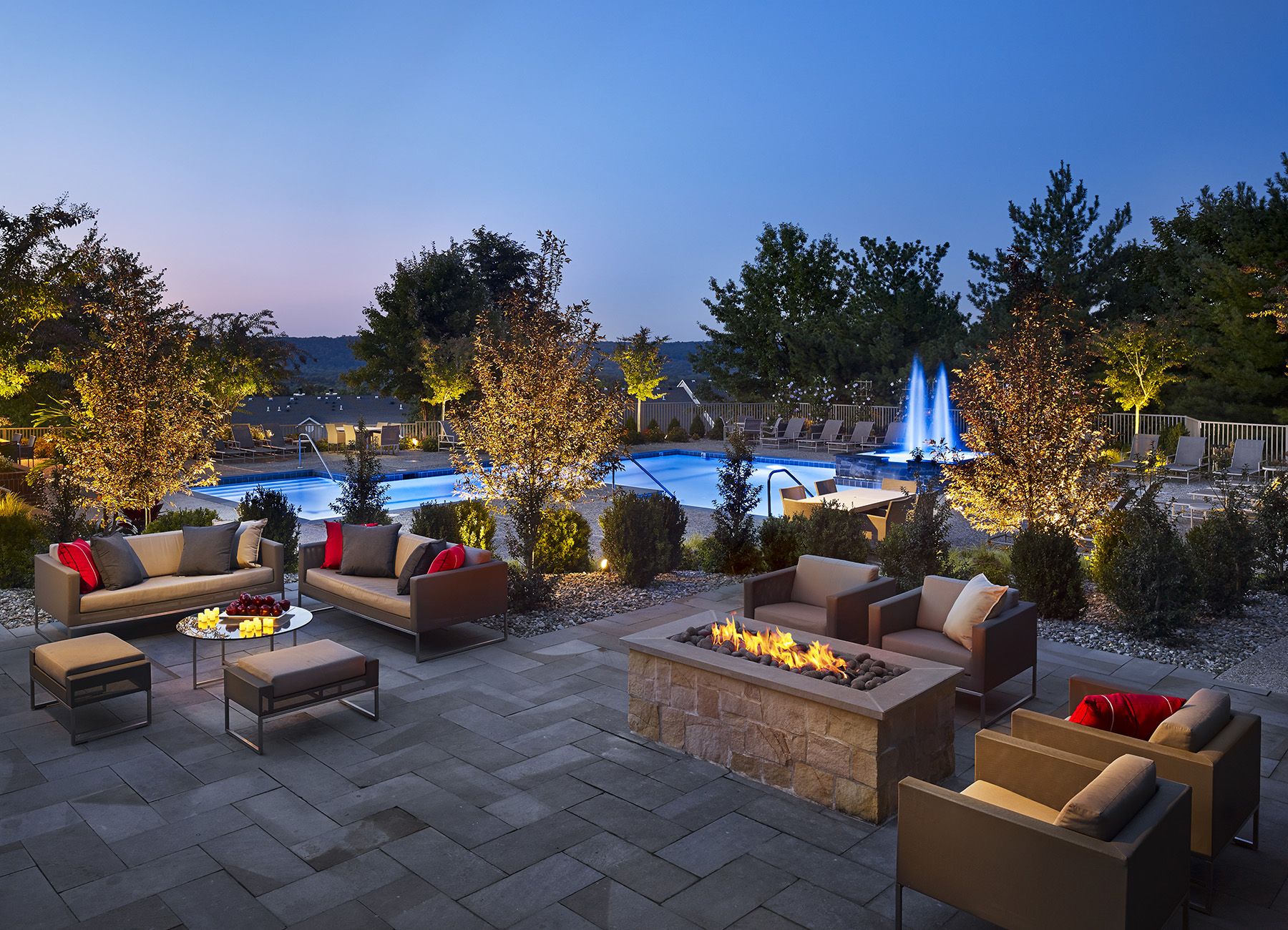 Firepit and lounge chairs in front of pool at night