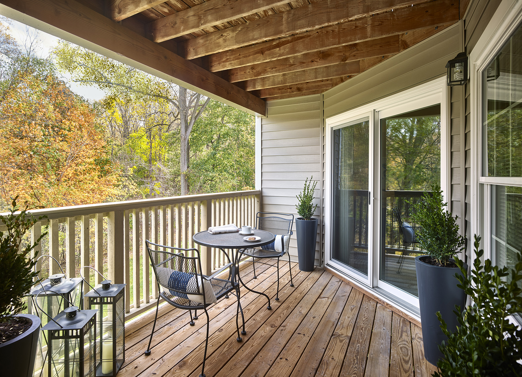 Wooden balcony with table looking out to changing leaves in forest