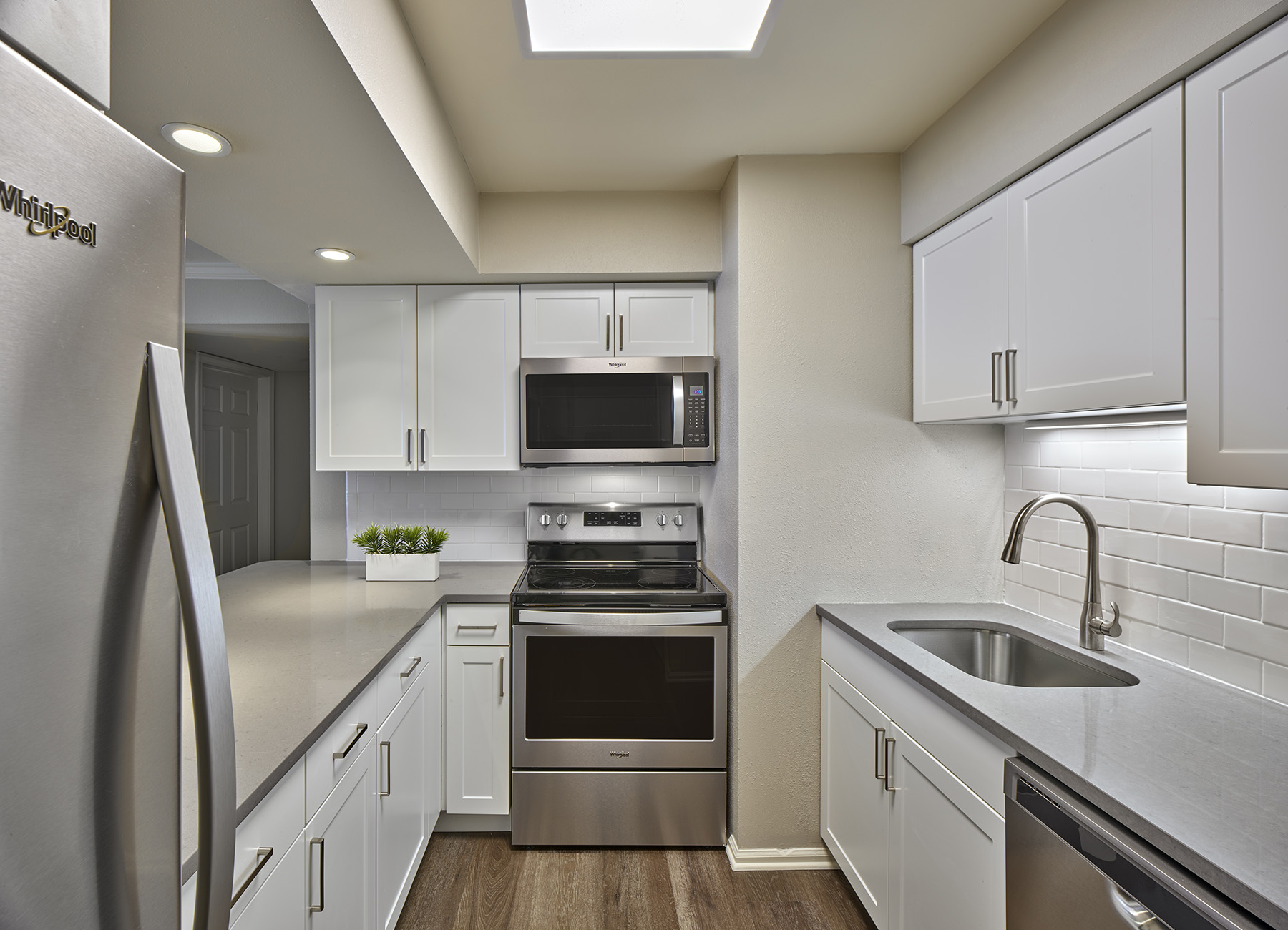 Galley kitchen with white cabinets and stainless steel appliances