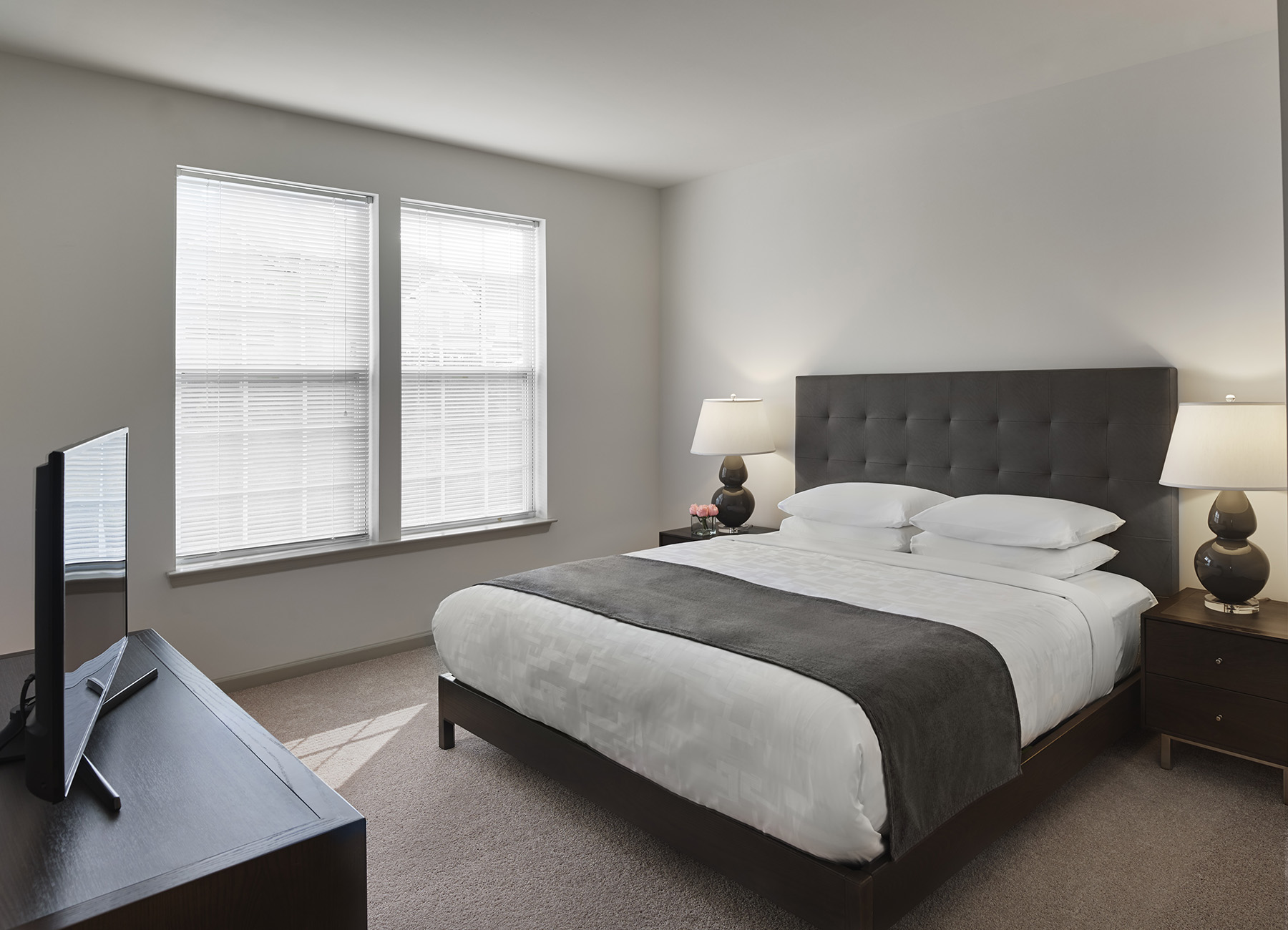 Bedroom with king bed, white sheets, dark gray blanket, and end tables