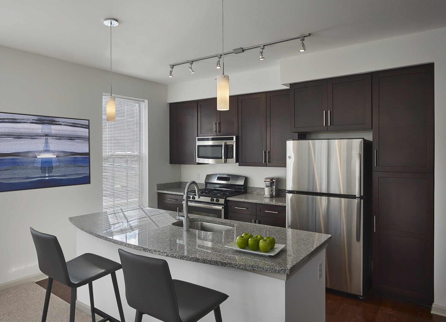 Kitchen island with bar stools, dark cabinets, and stainless steel appliances