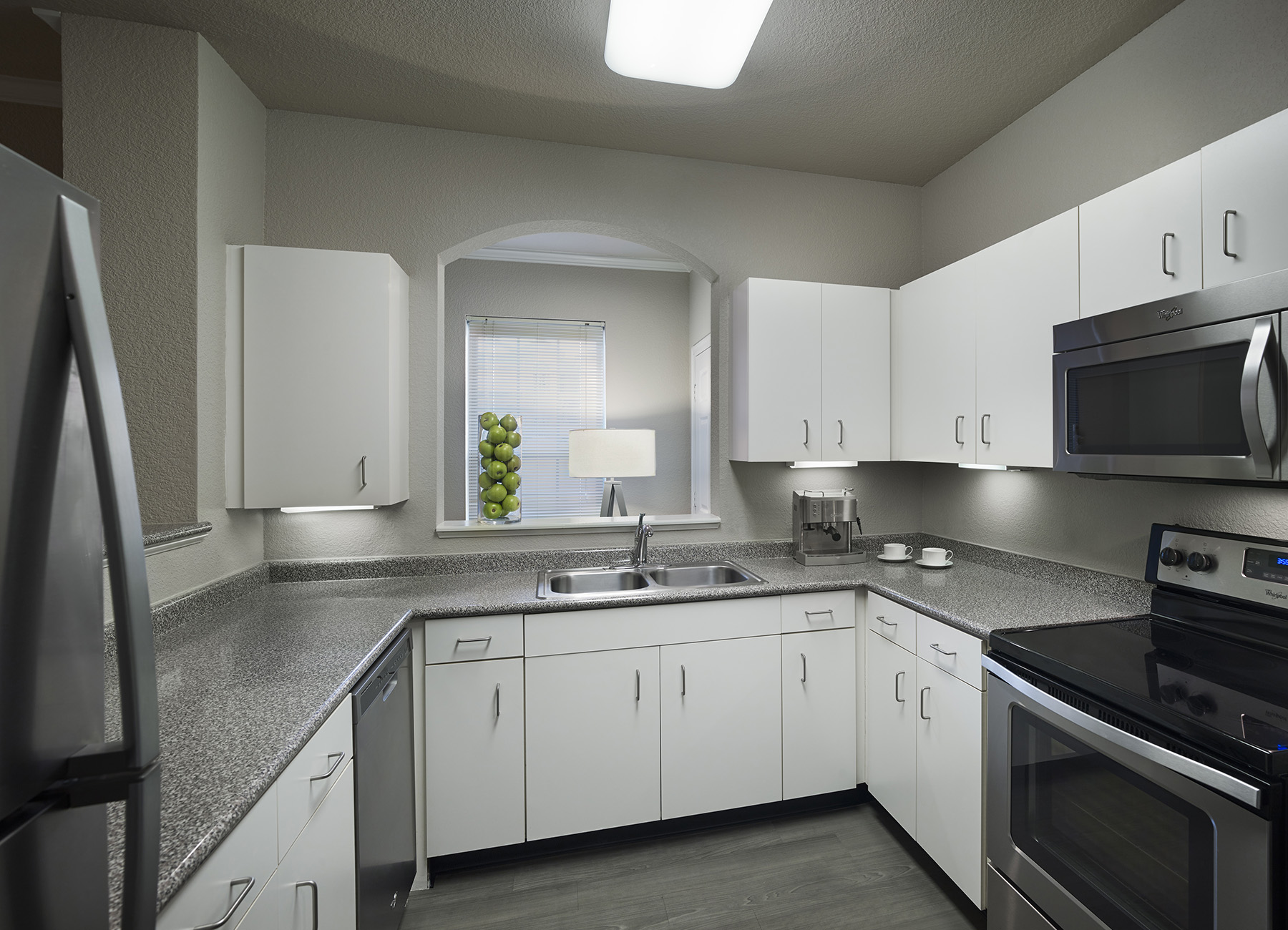 Kitchen with white cabinets and full sized appliances