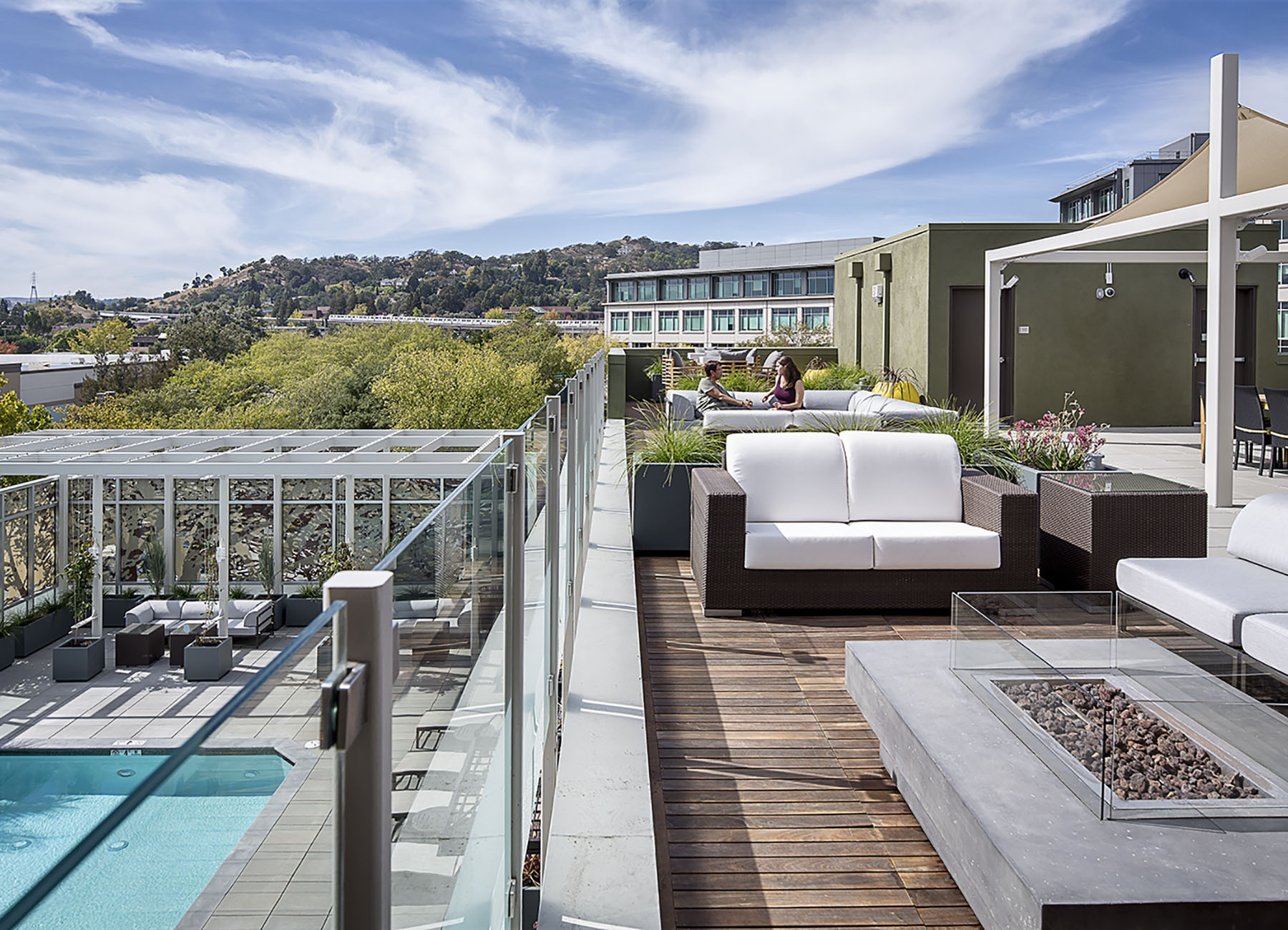 Rooftop terrace with firepit and seating overlooking an inground pool, with trees and commercial buildings behind